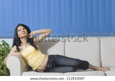 Young woman stretching on a couch