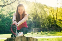 Young woman stretching outdoors in a park with flair sunny light.