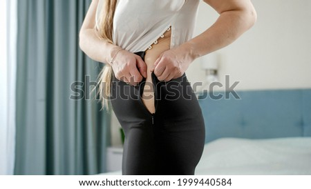 Young woman struggling to xip up tight dress. Concept of excessive weight, obese female, dieting and overweight problems. Stock photo ©