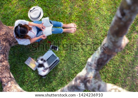 young woman student sitting in the grass of meadow under shadow of tree, reading a book with enjoying music online in feel relax and comfortable with puppy #1424236910
