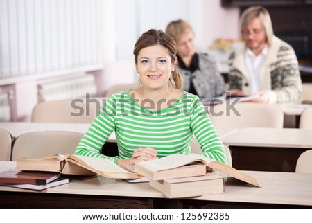 Young woman studying at desk with lots of books