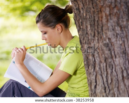young woman studying outdoors and leaning on tree. Copy space