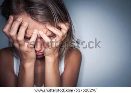Young woman suffering from a severe depression, anxiety/sudden fear (very harsh lighting is used on this shot to underline/convey the gloomy mood of the scene; color toned image)