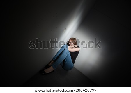 Young woman suffering from a severe depression, anxiety (very harsh lighting is used on this shot to underline the gloomy mood of the scene, color toned image)