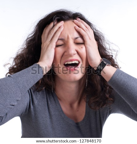 Young woman suffering from a terrible headache on a white background - stock photo