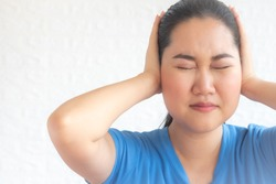 Young woman suffering from ear pain and tinnitus. Cause of earache includes otitis, earwax buildup, a foreign object in the ear, sinus infection.Ear disease concept,sticking plug fingers in ears.
