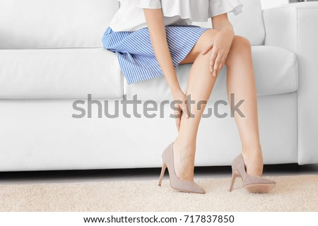Young woman suffering from leg pain at home #717837850