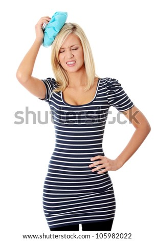 Young woman suffering from migraine headache applying to her head blue cold bag with ice. Long-haired blond girl in pain wearing striped long top and black trousers. Isolated on white background.