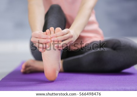 Young woman suffering from pain in foot while sitting on stretching mat, close up #566498476