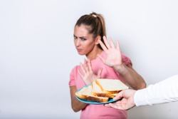 Young woman suffers from a gluten. Gluten intolerant and Gluten free diet concept, Real people. Copy space. Gluten intolerance and diet concept. Woman refuses to eat white bread. Focus on bread