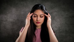 Young woman suffers from headache - studio photography
