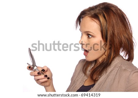 Young woman surprised at something on her cell phone - stock photo