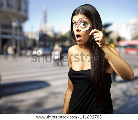 Young woman surprised looking through a magnifying glass at city