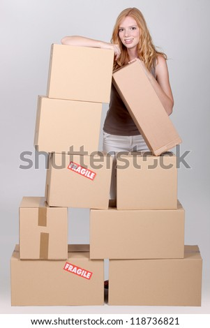 Young woman surrounded by cardboard boxes - stock photo