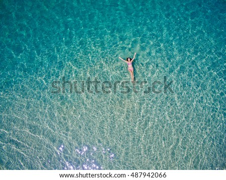 Young woman swimming in the blue sea. Top view. White beach, Phuket, Thailand. #487942066