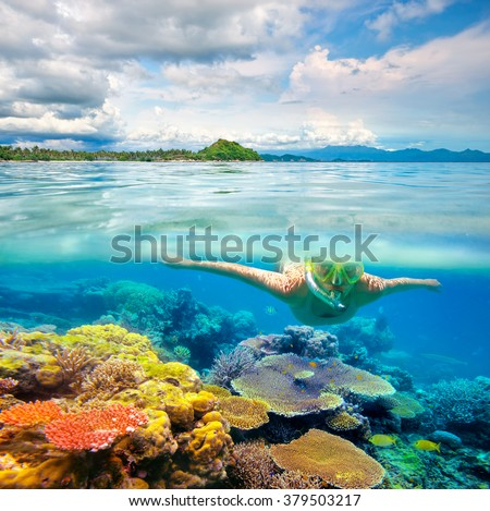 Young woman swimming on the bright coral reef in the sea on a background of a tropical beach. Lombok, Indonesia