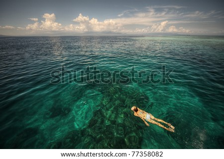 Young woman swimming over coral reef in transparent tropical sea. Bunaken island. Indonesia