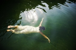 Young woman swimming under water in clear lake