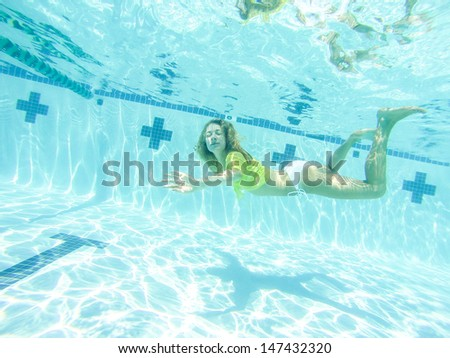 Young woman swimming underwater at swimming pool.