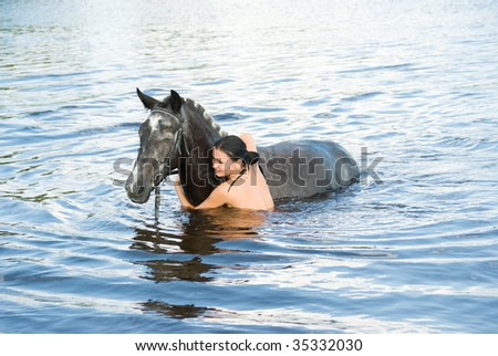 young woman swimming winth her black stallion in river