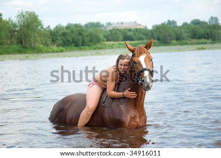 young woman swimming winth her stallion in in river