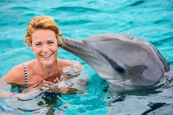 Young woman swimming with dolpin at a dolfinarium on a sunny day.