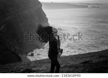 Young woman swinging and blowing long hair by the wind in a cliff while hiking in nature the sunset #1183618990