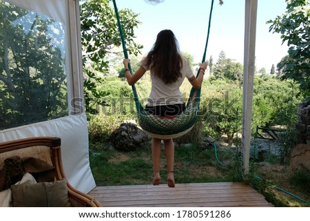 Young woman swinging in garden in Summer Stok fotoğraf ©