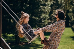 Young woman swinging with her daughter in the backyard