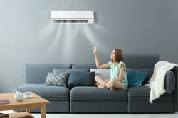 Young woman switching on air conditioner while sitting on sofa at home