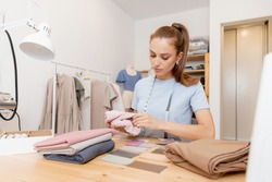 Young woman tailor fashion designer chooses shades of fabric and forms palette for tailoring fashionable clothes.