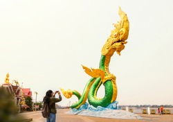 Young woman take photograph giant Naga at riverside