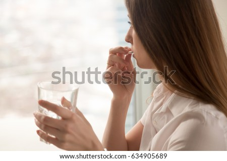 Young woman takes white round pill with glass of water in hand. Stressed female looking in window and drinking sedated antidepressant meds. Woman feels depressed, taking drugs. Medicines at work