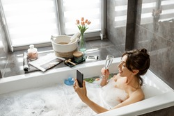 Young woman taking a bath, drinking sparkling wine, talking on phone, lying in bathtub with foam near the window at home