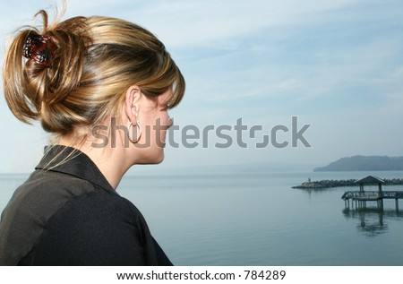 Young woman taking a break out by the lake.  Casual business attiire.  Looking out at water.