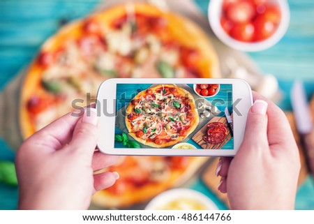 Young woman taking a photo of Pizza and Ingredients with smartphone