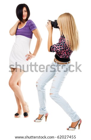 Young woman taking a picture of pretty girl, white background