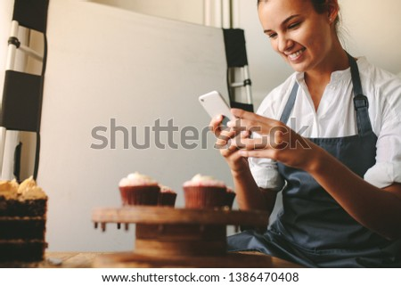 Young woman taking a pictures while cooking tasty pastry in the kitchen. Happy woman taking a picture of cupcakes on a wooden board with mobile phone while standing at the kitchen.