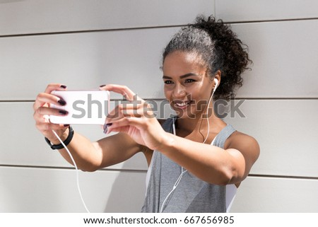 Young woman taking a selfie after workout, live streaming for social media