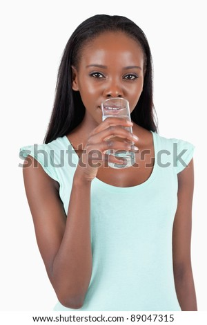 Young woman taking a sip of refreshing water against a white background