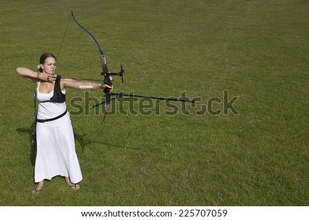 Young woman taking aim with her bow and arrow