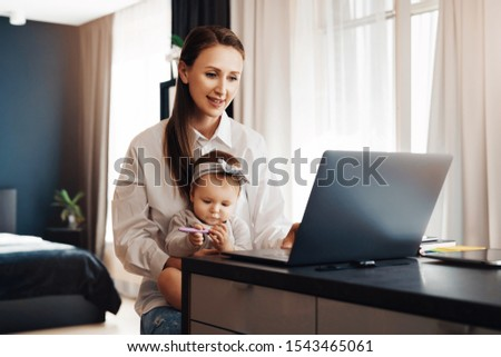 Young woman taking care of child at home and working remotely as digital company employee. Freelance distant work for specialists and professionals with children. Online solutions and programs for fun