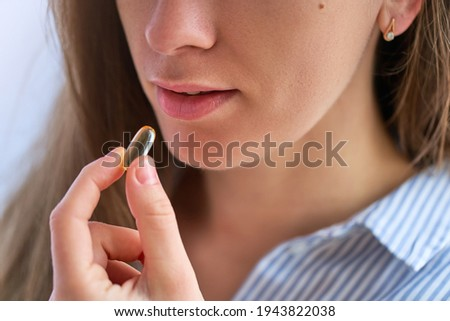 Young woman taking dietary supplement vitamin omega 3 for health. Fish oil softgel, vitamin D and vitamin C for support immunity and disease prevention