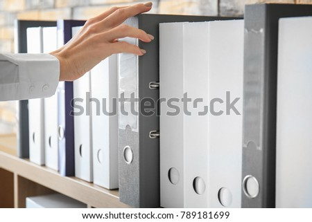 Young woman taking folder with documents from shelf in archive #789181699