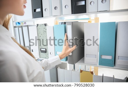 Young woman taking folder with documents from shelf in archive #790528030