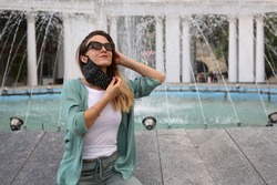 Young woman taking off face mask outside near the fountain at summer. Happy woman removing face mask and smiling.