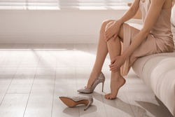 Young woman taking off shoes at home, closeup. Tired feet after wearing high heels