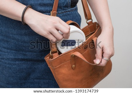 Young woman taking out/storing a silicone collapsible cup, reusable coffee tumbler from/into her handbag. #1393174739