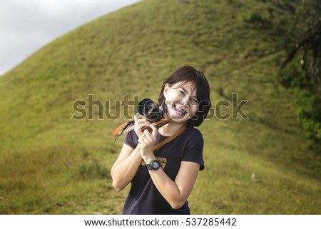 Young woman taking photo on the top of mountain with beautiful landscape.