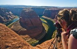 Young woman taking photograph of panoramic view of Horseshoe Bend at Utah, USA
